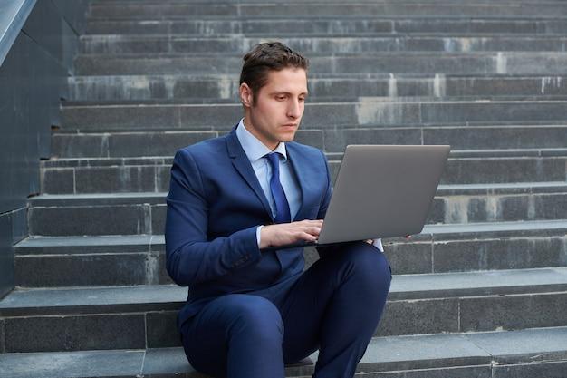 現代のラップトップに取り組んで、ビジネスセンターの外の階段に座って真剣に成功した青年実業家
