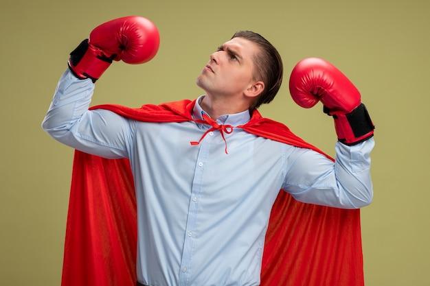 赤いマントとボクシンググローブで真面目なスーパーヒーローのビジネスマンは、光の壁の上に立っている強さと勇気を示す手を上げます