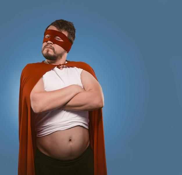 腕を組んでポーズ深刻なスーパーヒーローの男が赤いスーパーヒーローの衣装とマスクで自信を持ってひげを生やした男を渡った