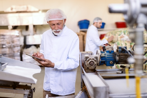 식품 공장에 서있는 동안 소금 스틱의 품질을 확인하는 손에 태블릿으로 멸균 된 제복을 입은 심각한 감독자.