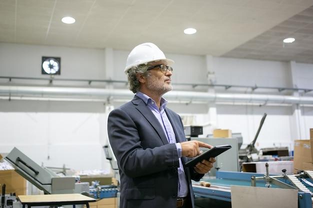 Серьезный руководитель в белом шлеме держит планшет и смотрит на производственный процесс