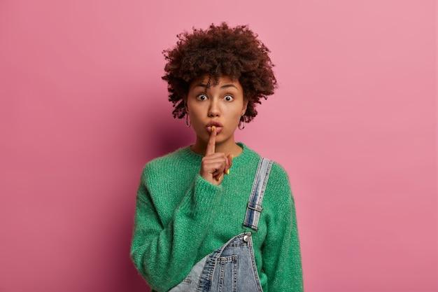 真面目な驚きの巻き毛の女性は沈黙を要求する