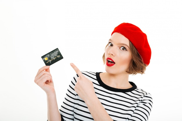 Serious surprised lady looking camera and pointing at credit card isolated