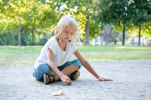 Serious sweet fair haired girl sitting and drawing with colorful pieces of chalks. copy space. childhood and creativity concept