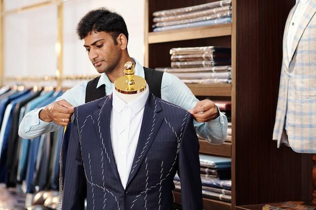 クライアントのスーツに取り組んでいるときにマネキンのオーダーメイドのジャケットをチェックする真面目な才能のある若いインドの仕立て屋