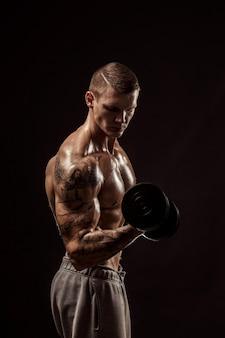 Serious tattoed shirtless athlete lifting dumbbells training on dark wall
