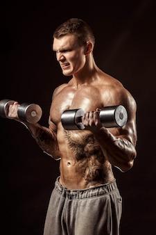 Serious tattoed shirtless athlete lifting metal dumbbells training on dark wall