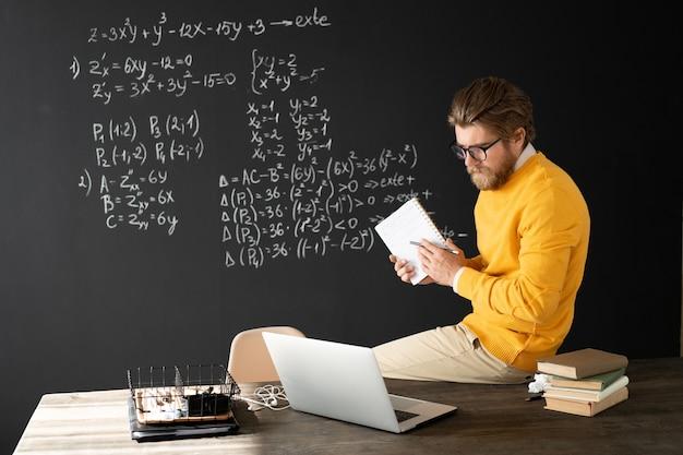 온라인 학생들에게 그것을 해결하는 방법을 설명하면서 분필 조각으로 칠판에 방정식을 가리키는 카피 북을 가진 심각한 교사