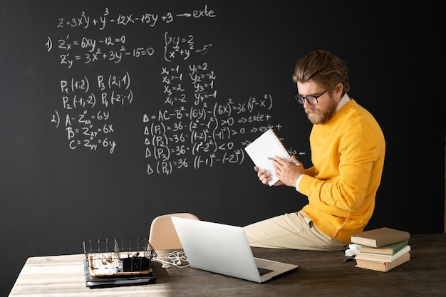 Serious teacher with copybook pointing at equation on blackboard with piece of chalk while explaining online students how to solve it