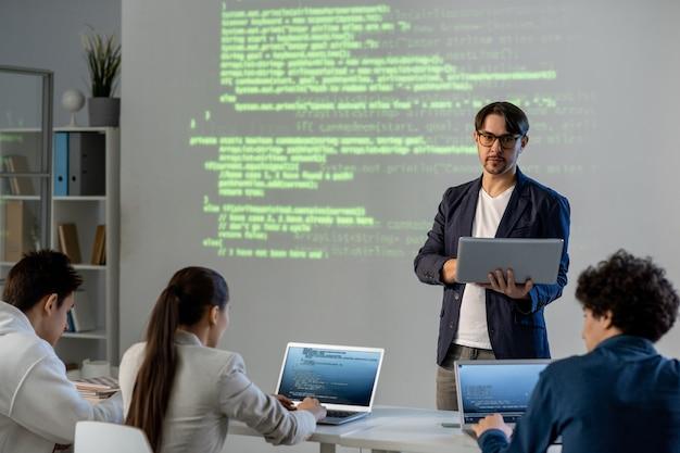 Серьезный учитель с ноутбуком стоит у доски с информацией и смотрит на группу студентов, готовящих свои проекты к конференции