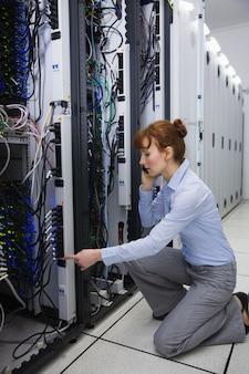 Серьезный техник разговаривает по телефону во время анализа сервера