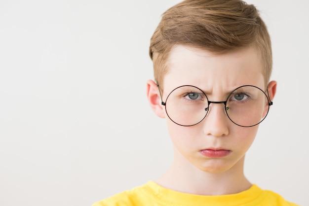 Серьезный мальчик-подросток с большими очками и желтой футболкой