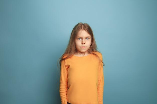 Ragazza teenager seria sull'azzurro. le espressioni facciali e le emozioni delle persone concetto