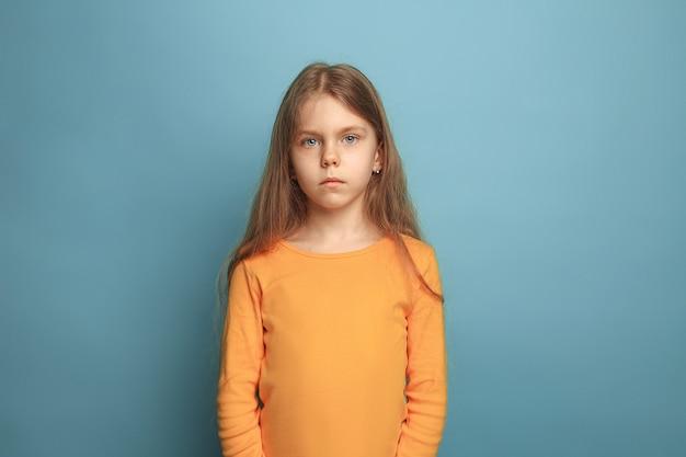 青いスタジオの背景に深刻な十代の少女。顔の表情と人々の感情の概念。