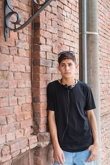 Serious teenage boy leaning on brick wall with black headphone surrounding his neck