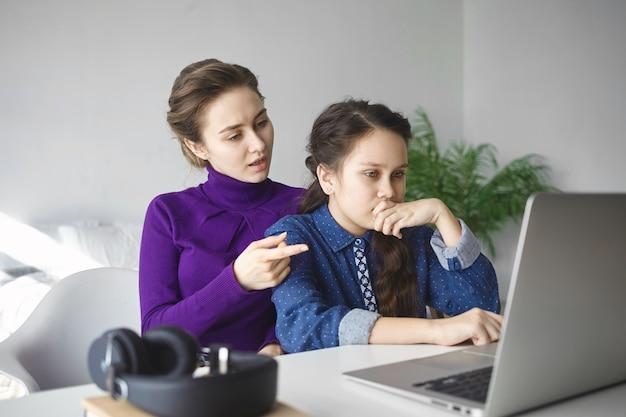 Серьезная девочка-подросток делает домашнее задание, проводит исследования, ищет информацию в интернете с помощью портативного компьютера, пока мать помогает ей,