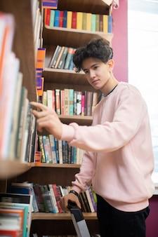 好奇心旺盛な何かを探している間、大学図書館の大きな本棚から本の1つを取る深刻な10代の男