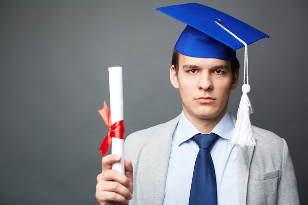 Серьезные подросток, подняв его сертификат