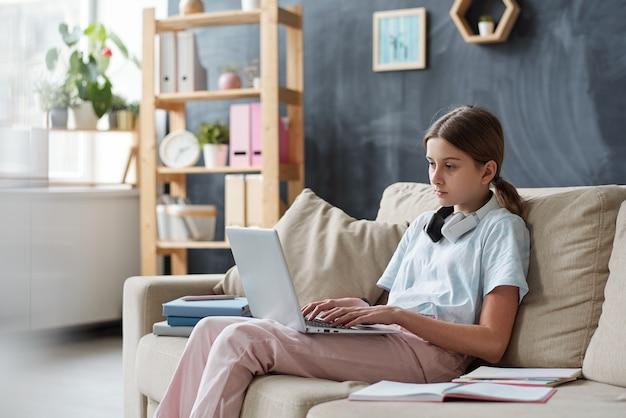 自宅の環境でソファに座って、検疫中にリモートで勉強しながらネットを閲覧しているラップトップを持つ深刻なティーンエイジャー