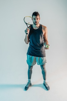 Serious tennis player hold ball and racquet. front view of young bearded european sportsman looking at camera. isolated on gray background with turquoise light. studio shoot. copy space