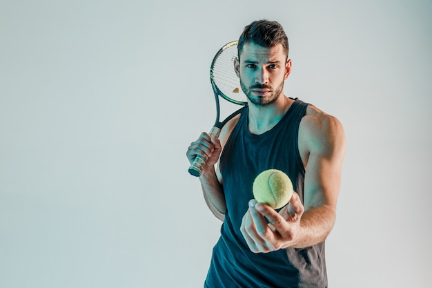 Serious tennis player hold racquet and showing ball at camera. front view of young bearded european sportsman looking at camera. isolated on turquoise background. studio shoot. copy space
