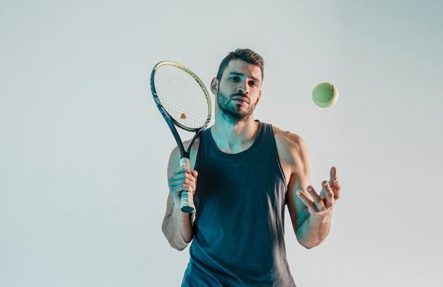 Serious tennis player hold racquet and throw up ball. front view of young bearded european sportsman looking at camera. isolated on gray background with turquoise light. studio shoot. copy space