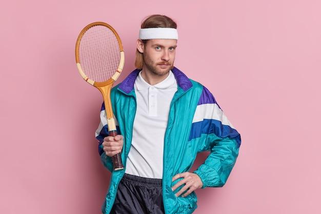 스포츠 장비를 갖춘 진지한 테니스 선수는 허리에 손을 대고 자신있게 게임을 준비하는 것처럼 보입니다.