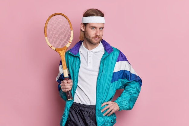 Serious tennis player with sport equipment keeps hand on waist looks confidently ready for game leads active lifestyle.