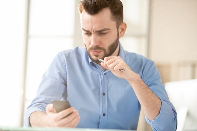 Serious or tense young office manager reading message or promo in smartphone that he cannot understand