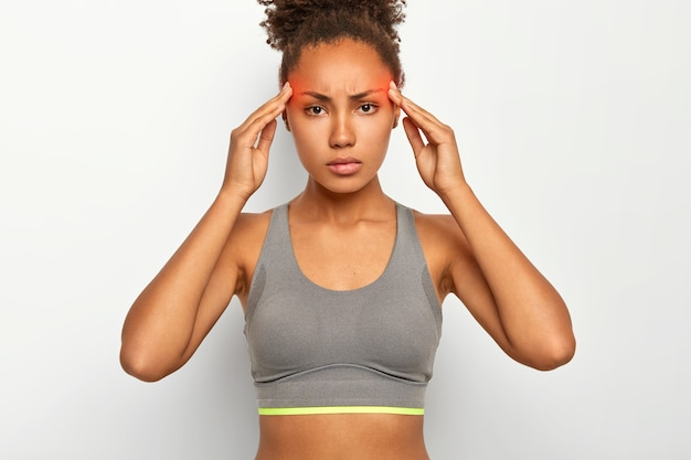 Serious tensed afro american woman suffers from terribe pain in temples, has migraine, being exhausted after long physical training, wears top, poses against white studio wall