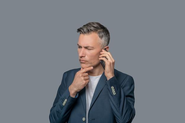 真面目な考え。スタジオで灰色の背景のあごに手を触れる耳の近くにスマートフォンを持つビジネス深刻な物思いにふける男