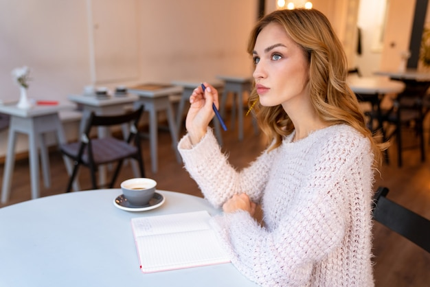 A serious thinking pretty young blonde woman sit in cafe indoors writing notes in notebook.
