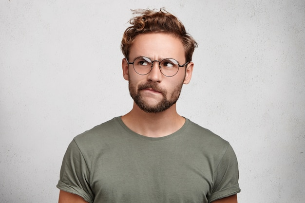 Serious thoughtful clever scientific worker wears spectacles, has beard, curves lower lip,