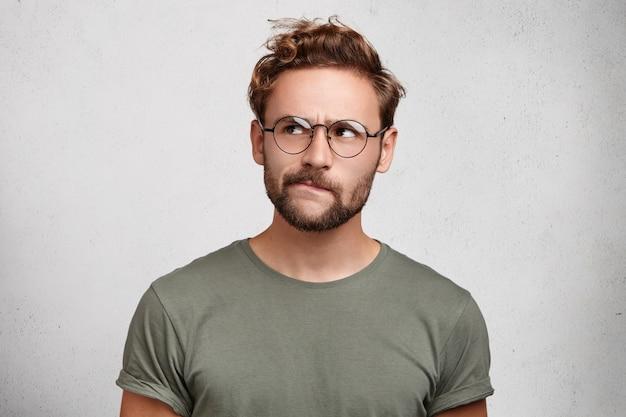 Il lavoratore scientifico serio e premuroso indossa occhiali, ha la barba, curva il labbro inferiore,
