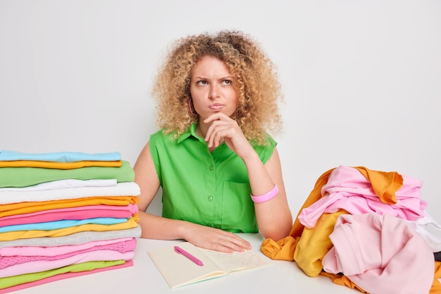 Serious thoughtful curly woman collects clothes for donation makes notes in diary surrounded by folded and unfolded laundry