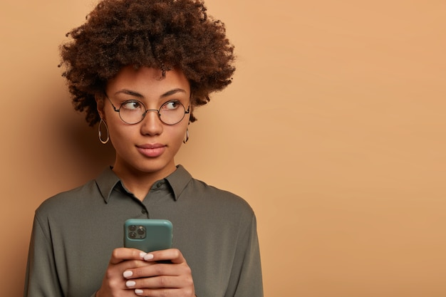 Serious thoughtful ethnic woman freelancer holds modern mobile phone in hands, sends message to colleague, works on distance, waits for call, wears shirt and round spectacles, browses internet