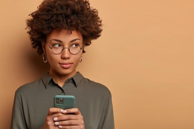 真面目で思いやりのあるエスニック女性フリーランサーは、現代の携帯電話を手に持ち、同僚にメッセージを送信し、距離を置いて作業し、電話を待ち、シャツと丸い眼鏡をかけ、インターネットを閲覧します