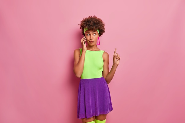 La donna seria e premurosa alla moda dalla pelle scura parla tramite telefono cellulare, punta il dito indice sopra, indossa abiti luminosi