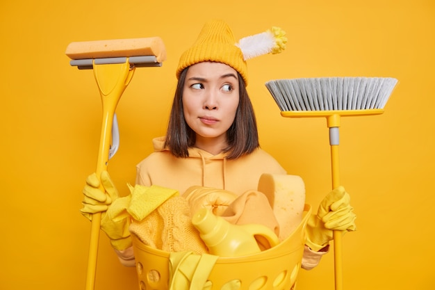 Serious thoughtful female maid holds mop and broom in both hands busy doing household chores poses near laundry basket has brush stuck in hat isolated over vivid yellow background. domestic workload