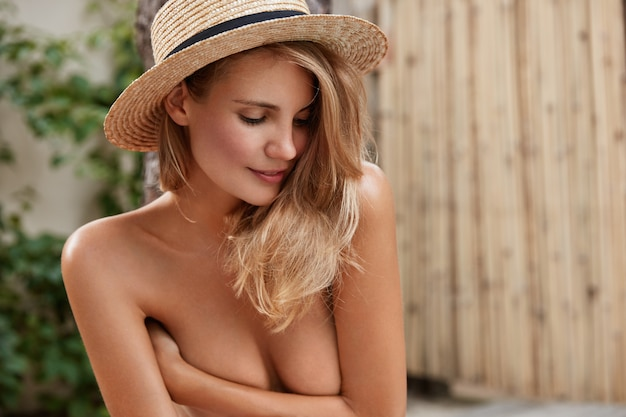 Serious thoughtful female model hides breast with hands, has healthy pure skin, looks pensively down, wears straw summer hat, poses outdoor. naked young woman slim perfect body shape