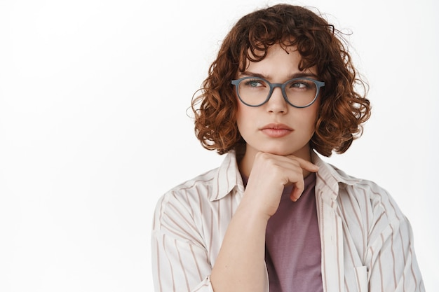 Serious thoughtful girl in glasses, student thinking, looking left at copy space and pondering, making decision, having a thought, standing on white