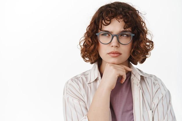 Серьезная задумчивая девушка в очках, студент думает, смотрит влево на пространство для копирования и размышляет, принимает решение, имеет мысль, стоит на белом
