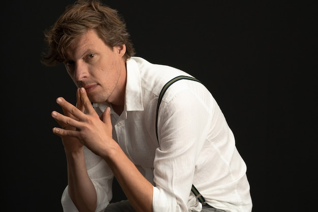 Serious thoughtful man sits in thinking position. shaggy caucasian guy wearing a white shirt and suspenders isolated on black wall with copy space at right.
