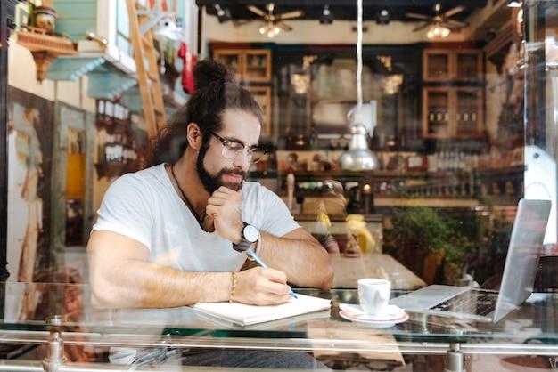 Серьезный вдумчивый человек, сидящий перед ноутбуком во время работы в кафе