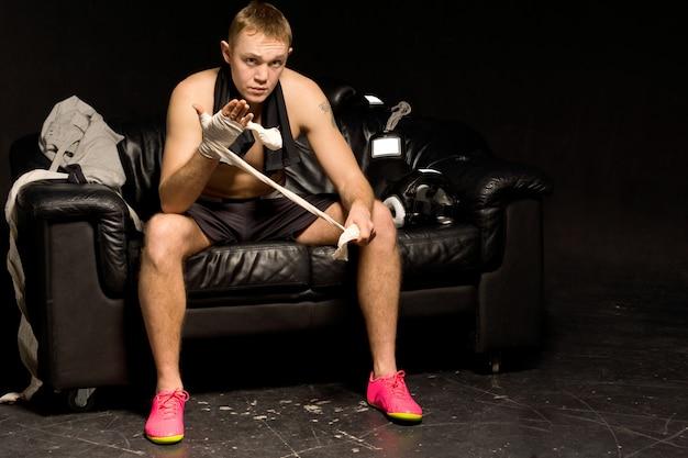 真剣に思慮深い筋肉質の若いボクサーが戦いの準備をしている