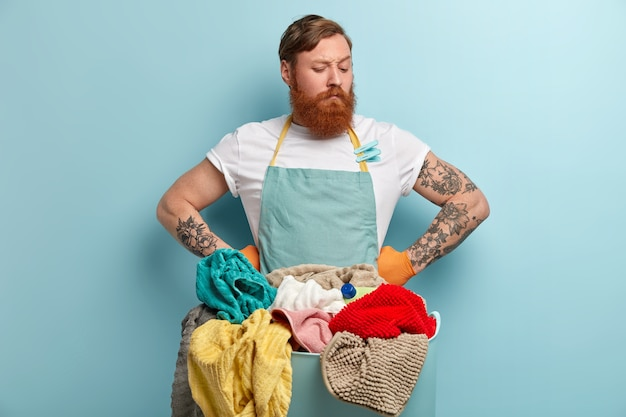 Serious thoughtful redhead man holds both hands on waist, has thick bristle, looks down, wears casual t shirt and apron, stands in front of basin with laundry and cleaning supply isolated on blue wall