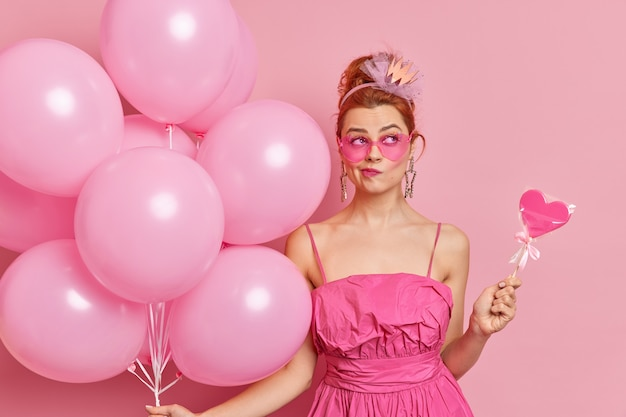 Serious thoughtful redhead woma purses lips thinks about celebration wears trendy sunglasses and dress holds sweet candy and balloons prepares for graduation party