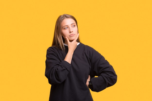 Serious thoughtful woman is touching her chin while thinking.