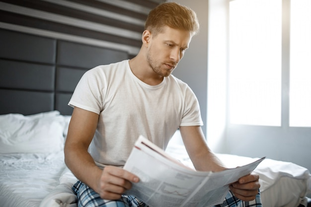 Serious thoughtful young man on bed early morning. he read newspaper.