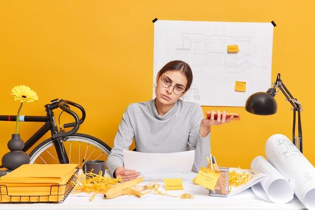심각한 피곤한 여자는 종이 스케치를 보유하고 있으며 데스크톱에서 스마트 폰 포즈를 취하고 브레인 스토밍 회의 또는 동료들과 브리핑을 준비하고 거의 청사진에 대한 엔지니어링 프로젝트 작업을 마쳤습니다.